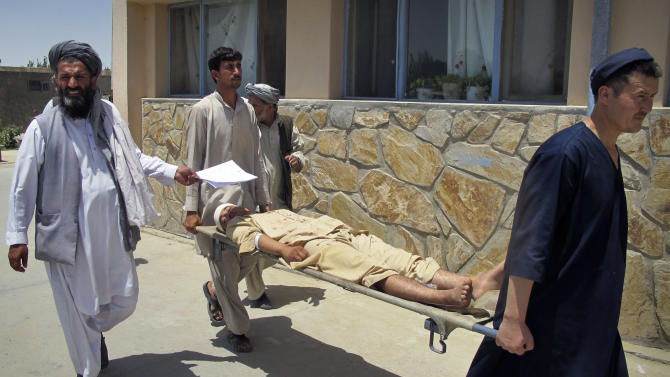 Afghans carry a victim of a suicide attack to a hospital in Kunduz, north of Kabul, Afghanistan, Sunday, June 19, 2011. A suicide car bomber struck a German military convoy in northern Afghanistan on Sunday, detonating explosives that killed three Afghan civilians and overturned at least one armored vehicle, according to officials and witnesses. (AP Photo/Fulad Hamdard)
