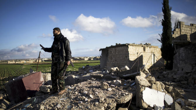A Free Syrian Army fighter walks over the ruins of a building bombed by a Syrian Army jet in Fafeen village, north of Aleppo province, Syria, Tuesday, Dec. 11, 2012. Syrian rebels including Islamic extremists took full control of a sprawling military base Tuesday after a bloody two-day battle that killed dozens of soldiers, activists said. It was the latest gain by opposition forces bolstered by an al-Qaida-linked group that has provided skilled fighters but raised concerns in the West. (AP Photo/Manu Brabo)