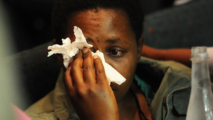 A woman cries after watching footage of South African police shooting at the Lonmin mine, in Marikana, during an official inquest in Rustenburg,  South Africa, Tuesday Oct 23, 2012. Graphic video footage of South African police shooting dead 34 protesting mine strikers in August left the victims' widows weeping inconsolably when it was shown to an official inquest Tuesday. The Marikana Commission, which is investigating violence at Lonmin's platinum mines on Aug. 16 as well as related incidents in which up to 46 people were killed, was disrupted by the emotional response of grieving family members to the video footage which shows some of the worst state violence since the end of apartheid since 1994.  (AP Photo)