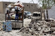 Iraqis collect their belongings amidst the rubble of destroyed houses following a series of bomb attacks inTaji. A wave of nationwide violence saw 113 people killed and 250 wounded in Iraq's deadliest day in two and a half years