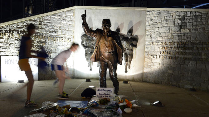 July 22 People visit the Joe Paterno statue early Sunday July 22, 2012. in State College, Pa. The famed statue of Paterno was taken down from outside the Penn State football stadium Sunday morning, eliminating a key piece of the iconography surrounding the once-sainted football coach accused of burying child sex abuse allegations against a retired assistant. (AP Photo/John Beale)