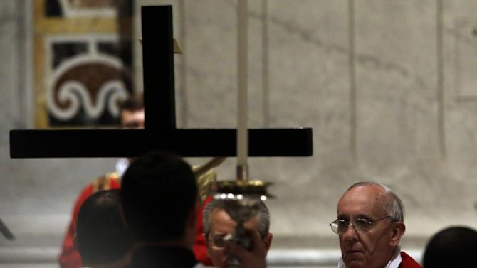 Pope Francis, right, looks up to the Crucifix during the Passion of Christ Mass inside St. Peter's Basilica, at the Vatican, Friday, March 29, 2013. Pope Francis began the Good Friday service at the Vatican with the Passion of Christ Mass and hours later will go to the ancient Colosseum in Rome for the traditional Way of the Cross procession. (AP Photo/Gregorio Borgia)