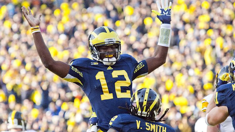 Michigan quarterback Devin Gardner (12) celebrates a touchdown with running back Vincent Smith (2) during the second quarter of an NCAA college football game against Iowa, Saturday, Nov. 17, 2012, in Ann Arbor, Mich. (AP Photo/Tony Ding)