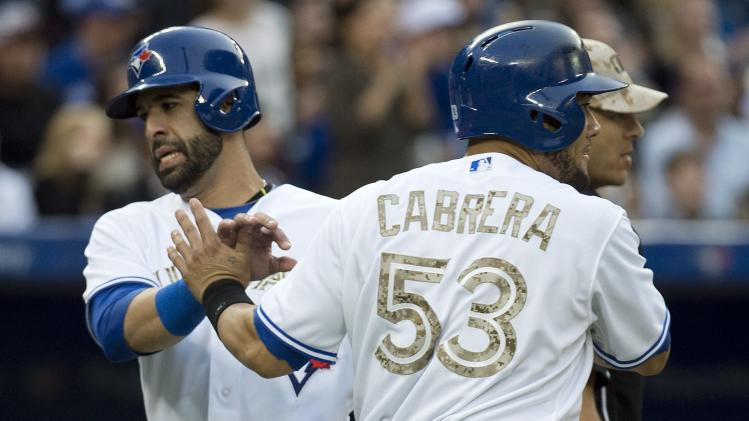 Toronto Blue Jays right fielder Jose Bautista, left, celebrates his scored run with teammate Melky Cabrera, right, while playing against the Atlanta Braves during third inning interleague baseball action in Toronto on Monday, May 27, 2013. (AP Photo/The Canadian Press, Nathan Denette)