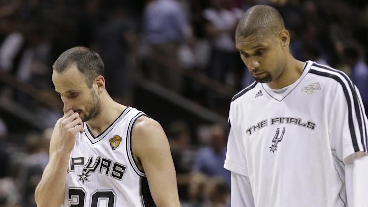 San Antonio Spurs' Manu Ginobili, of Argentina,, left, and Tim Duncan leave the floor after losing to the Miami Heat at Game 4 of the NBA Finals basketball series, Thursday, June 13, 2013, in San Antonio. The Heat won 109-93. (AP Photo/Eric Gay)