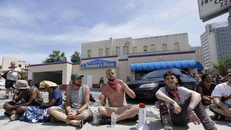 "A few demonstrators sit on a Domino's Pizza parking lot in protest, Thursday, Aug. 30, 2012, in Tampa, Fla. The three dozen chanting anti-GOP protesters hit a lull of silence as they marched through a neighborhood of low-income housing in west Tampa. ""What are you guys doing taking a nap?"" shouted one protester to his cohorts. Another shouted, ""You guys are reeeeaaal quiet, now!""  The protests against the Republican convention in Tampa have been unexpectedly muted this week, something even the protesters acknowledge. (AP Photo/Chris O'Meara)"