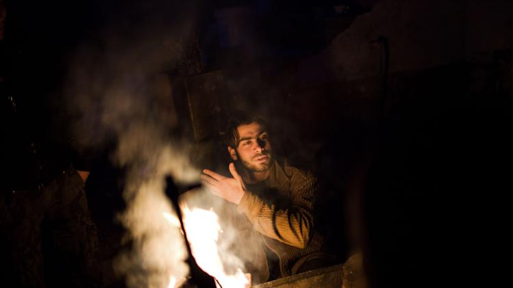 FSA fighters warm themselves up  by the fire in Tal Sheen  village, north of Aleppo province, Syria, Wednesday, Dec 12, 2012 (AP Photo / Manu Brabo)