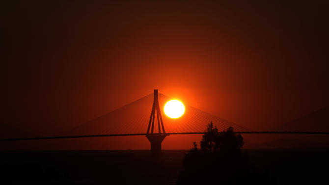 The sun sets behind the 560-meter Charilaos Trikoupis bridge in near the city of Patras in Southern Greece on Friday Sept. 27, 2013. The bridge connecting the Greek mainland to the Peloponnese area was opened in 2004, shortly before the 2004 Olympic Games in Athens. A flame lighting ceremony for the Winter Games in Sochi, Russia will take south of Patras on Sunday, at ancient Olympia. (AP Photo/Dimitri Messinis)