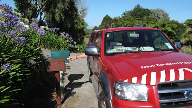 In this Friday, Feb. 15, 2013 photo, postman John Lahmert delivers mail in rural Otaki, New Zealand. New Zealand is considering cutting letter deliveries from six days a week to three as global demand for postal services dwindles. (AP Photo/Nick Perry)