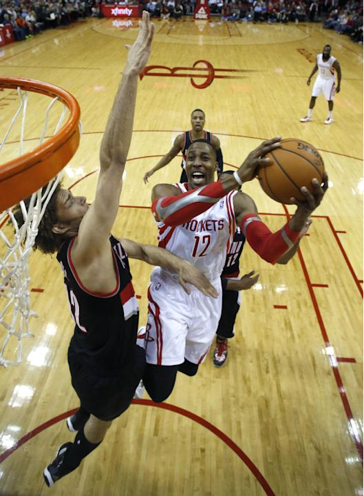 Houston Rockets' Dwight Howard (12) goes up to shoot as Portland Trail Blazers' Robin Lopez defends during the first quarter of an NBA basketball game on Sunday, March 9, 2014, in Houston
