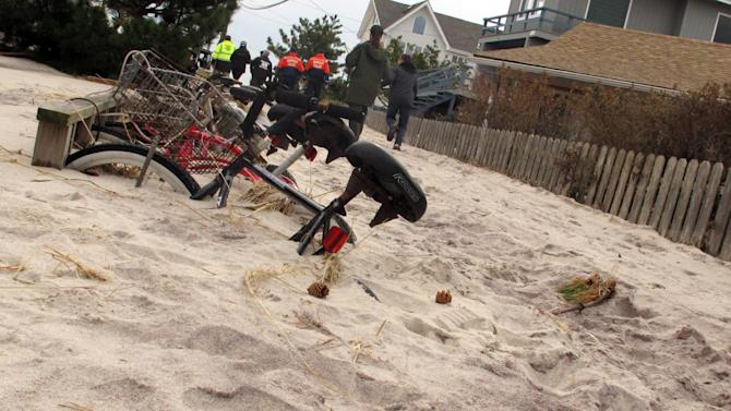 In this Friday, Nov. 16, 2012 photo, bicycles remain buried beneath several feet of sand in the Fire Island community of Kismet, N.Y. In the background, Suffolk County and other officials tour the community damaged from Superstorm Sandy. (AP Photo/Frank Eltman)