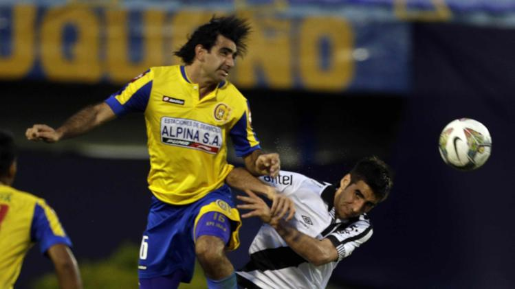 Castro of Danubio and Irala of Deportivo Capiata fight for the ball during their Copa Sudamericana soccer match in Luque