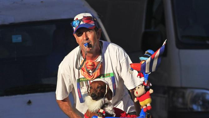 A street entertainer for tourists rides his bicycle with his dog in Havana