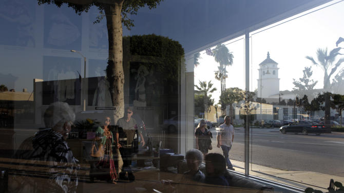Fullerton Police Station, background right, is seen as people gather in the lobby of a theater in Fullerton, Calif., Thursday, Aug. 18, 2011. Until last month, the most pressing political issue in the Southern California suburb of Fullerton was a debate over whether to build homes and retail on hundreds of acres of rolling hills north of the city. Today, the historic town that's home to five colleges and a vibrant nightlife is the target of international outrage after a mentally ill homeless man died following a violent fight with six police officers that was captured on camera. (AP Photo/Jae C. Hong)