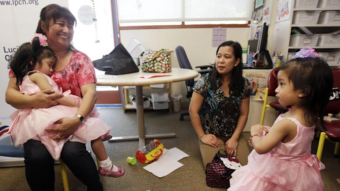 Angelina Sabuco, 2, far left, sleeps in the arms of her aunt Marites Sabuco as her mom Ginady, center right, and twin sister Angelica, far right, look on at Lucile Packard Children's Hospital Monday, April 30, in Palo Alto, Calif.  The twin sisters, who were born joined in the chest and abdomen, were separated by doctors at the Palo Alto hospital during an intricate 10-hour procedure on December 2011. (AP Photo/Marcio Jose Sanchez)
