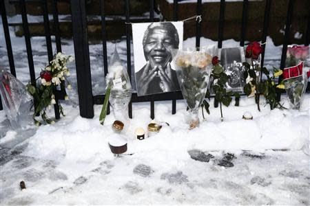 Flowers and candles are seen in the snow around pictures of Nelson Mandela outside the South-African embassy in Oslo