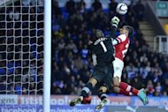 Reading's goalkeeper Adam Federici (L) clears the ball under pressure from Arsenal's Marouane Chamakh (R) during extra time in their English League Cup fourth round match at The Madejski Stadium in Reading. Arsenal won the game 7-5