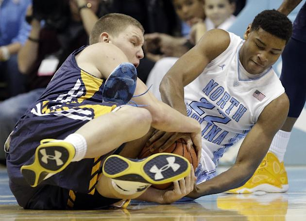 North Carolina's Isaiah Hicks (22) and UNC Greensboro's  Jordy Kuiper struggle for possession of the ball during the first half of an NCAA college basketball game in Chapel Hill, N.C., Saturda