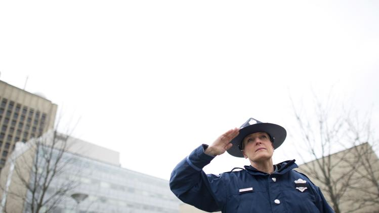 A Massachusetts State Police member salutes during the singing of the national anthem at a memorial service for Collier in Cambridge