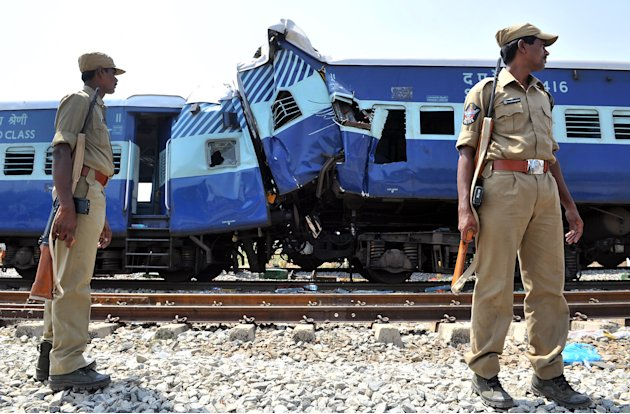 Railway officials oversee the clear up operation of the mangled remains of the Bangalore-bound Hampi Express after it collided with a stationary goods train near Penneconda town in Ananthpur District,