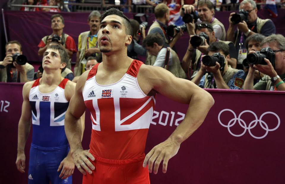 Britain's silver medallist gymnast Louis Smith, right, and bronze medallist gymnast Max Whitlock look at the scoreboard for final scores for the artistic gymnastics men's pommel horse finals at the 2012 Summer Olympics, Sunday, Aug. 5, 2012, in London.  (AP Photo/Julie Jacobson)