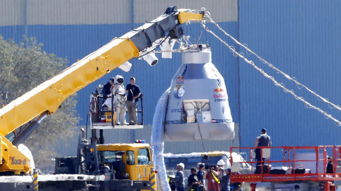 Felix Baumgartner, in pressurized suit on platform at left, prepares to enter the balloon capsule in Roswell, N.M. on Tuesday, Oct. 9, 2012. Baumgartner will attempt to break the speed of sound with his own body by jumping from the space capsule lifted by a 30 million cubic foot helium balloon. Baumgartner plans to jump from an altitude of 120,000 feet - an altitude chosen to enable him to achieve Mach 1 in freefall - which will deliver scientific data to the aerospace community about human survival from high altitudes. (AP Photo/Matt York)