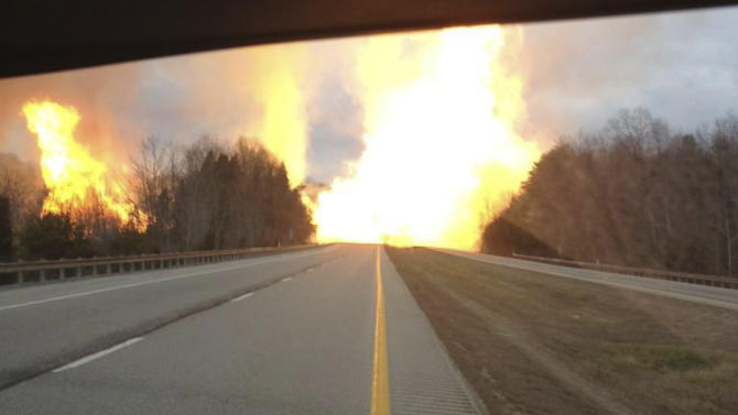 This image provided by the Kanawha County Emergency Services shows flames erupting across Interstate 77 from a gas line explosion in Sissonville, W. Va., Tuesday Dec. 11, 2012. At least five homes went up in flames Tuesday afternoon and a badly damaged section of Interstate 77 was shut down in both directions near Sissonville after a major gas line explosion triggered an hour-long inferno that officials say spanned about a quarter-mile.   (AP Photo/Kanawha County Emergency Services)