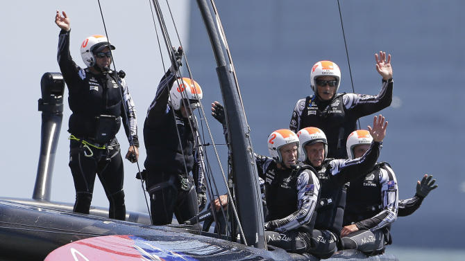 Crew members aboard Emirates Team New Zealand wave after winning the fourth race of their America's Cup challenger series final sailing event against Luna Rossa Challenge, of Italy, Wednesday, Aug. 21, 2013, in San Francisco. Emirates Team New Zealand won both of their two races Wednesday. Skipper Dean Barker, right, looks on. (AP Photo/Eric Risberg)