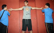 Officials measure Junmar Fajardo's wingspan. (PBA Images)
