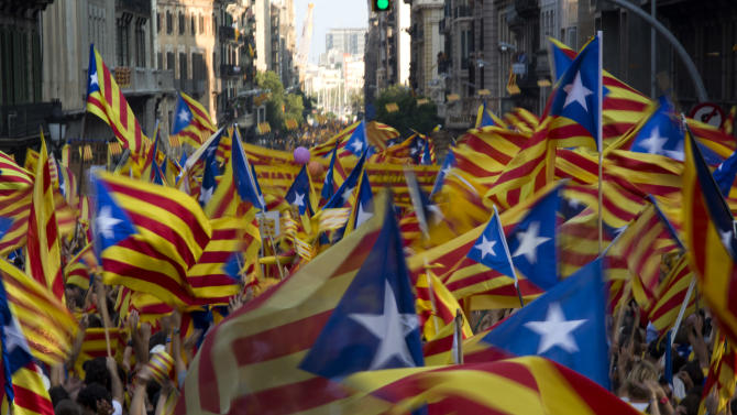 """FILE- In this  Sept. 11, 2012, file photo, demonstrators wave Catalan flags during a protest rally demanding independence for Catalonia, in north-eastern Spain, on the Catalan national day, in Barcelona, Spain. More than ever, FC Barcelona, known affectionately as Barca, lived up to its motto of being """"more than a club"""" for this wealthy northeastern region where Spain's economic crisis is fueling separatist sentiment. Barca has been seen as a bastion of Catalan identity dating back to the three decades of dictatorship when Catalans could not openly speak, teach or publish in their native Catalan language. Barcelona writer Manuel Vazquez Montalban famously called the football team """"Catalonia's unarmed symbolic army.""""(AP Photo/Emilio Morenatti, File)"""