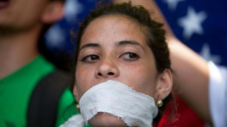 A demonstrator covers her mouth with a rag to prostest government censorship, during a march to Venezuelan Telecommunications Regulator Office or CONATEL in Caracas, Venezuela, Monday, Feb17, 2014. Students, who've spent the past week on the streets alternating between peaceful protests by day and battles with police at night, marched on Monday to Venezuela's telecom regulator to demand it lift all restrictions on the media's coverage of the unfolding political crisis. (AP Photo/Alejandro Cegarra)