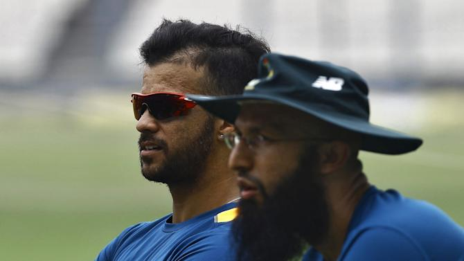 South Africa's Duminy sits along with his teammate Amla during a practice session ahead of their Twenty20 cricket match against India in Kolkata