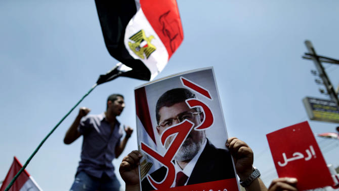 """Opponents of Egypt's Islamist President Mohammed Morsi hold posters with Arabic that reads, """"Leave,"""" as they protest outside the presidential palace in Cairo, Egypt, Sunday, June 30, 2013. Organizers of a mass protest against Morsi claimed Saturday that more than 22 million people have signed their petition demanding the Islamist leader step down, asserting that the tally was a reflection of how much the public has turned against his rule. (AP Photo/Hassan Ammar)"""