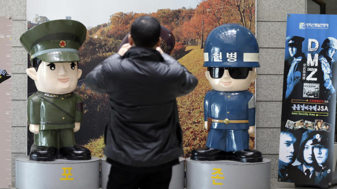 A man takes pictures of dolls of South, right, and North Korean soldiers on display at the Unification Observation Post near the demilitarized zone (DMZ) between the two Koreas in Paju, north of Seoul, South Korea, Thursday, March 28, 2013. A day after shutting down a key military hotline, Pyongyang instead used indirect communications with Seoul to allow South Koreans to cross the heavily armed border and work at a factory complex that is the last major symbol of inter-Korean cooperation. (AP Photo/Lee Jin-man)