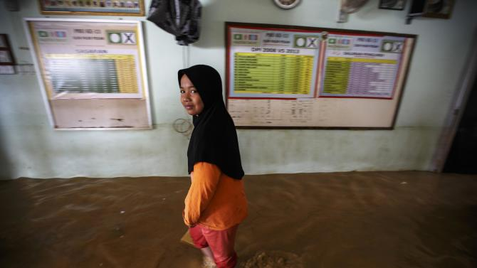 A girl walks inside her flooded house on the outskirt of Kota Bharu in Kelantan