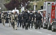 SWAT police walk through at a private religious college in Oakland, California after a gunman went on a shooting rampage. The suspect -- a local ethnic Korean resident who surrendered soon after the attacks -- stood up in a classroom at Oikos University in East Oakland and shot one person at point blank range in the chest, then sprayed the room with bullets, a witness recounted.