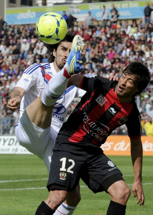 Lyon's Milan Bisevac fights for the ball with OGC Nice's Dario Cvitanich during their French Ligue 1 soccer match at Le Ray stadium in Nice
