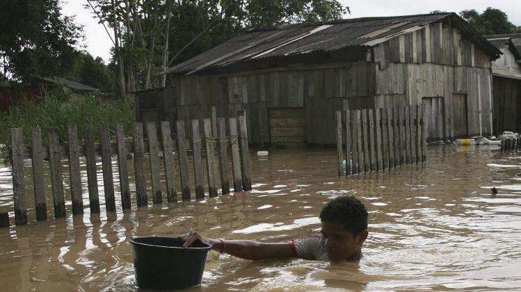 A resident walks through floodwaters from the Acre river in Rio Branco