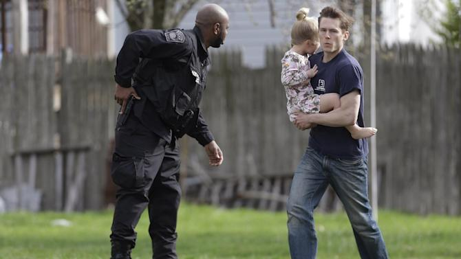 A police officer evacuates a shoeless man holding a child as members of law enforcement conduct a search for a suspect in the Boston Marathon bombings, Friday, April 19, 2013, in Watertown, Mass.  The two suspects in the Boston Marathon bombing killed an MIT police officer and hurled explosives at police in a car chase and gun battle overnight that left one of them dead and his brother on the loose, authorities said Friday as thousands of officers swarmed the streets in a manhunt that all but paralyzed the Boston area.  (AP Photo/Matt Rourke)