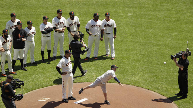 Tyler Stow, son of Bryan Stow who was beaten at Dodger Stadium last year, throws out the ceremonial first pitch as Giants pitcher Jeremy Affeldt looks on before the start of the San Francisco Giants Opening Day baseball game against the Pittsburgh Pirates in San Francisco, Friday, April 13, 2012. (AP Photo/Eric Risberg)