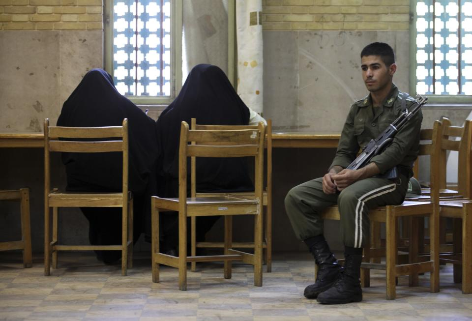 Two Iranian women fill in their ballots for the presidential and municipal councils elections as a policeman sits in a polling station in Tehran, Iran, Friday, June 14, 2013. (AP Photo/Vahid Salemi)