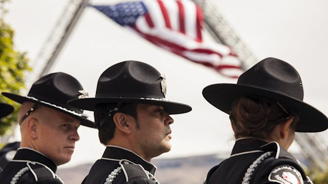 Members of the Yakima Police Honor Guard wait for the arrival of fallen firefighters Zbyszewski, Zajac, and Wheeler, who died fighting the Okanogan Complex fire, during their memorial in Wenatchee, Washington