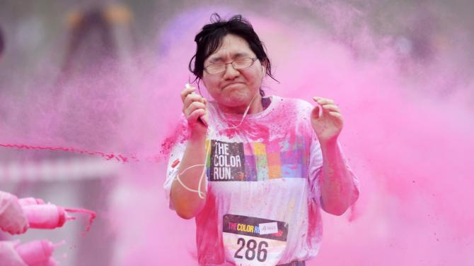 A woman reacts as she is sprayed with colour powder during a five-kilometre colour run event in Beijing