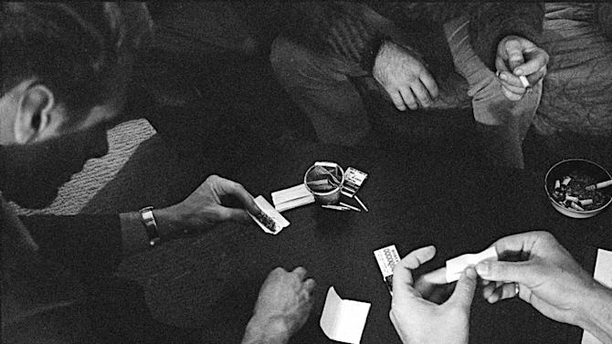 """FILE - In this May 23, 1966, file photo, people roll joints at a marijuana party near the University of California at Berkeley campus in Berkeley, Calif. In 2012, Washington state and Colorado voted to legalize and regulate its recreational use. But before that, the plant, renowned since ancient times for its strong fibers, medical use and mind-altering properties, was a staple crop of the colonies, an """"assassin of youth,"""" a counterculture emblem and a widely accepted - if often abused - medicine. On the occasion of  """"Legalization Day,"""" Thursday, Dec. 6, 2012, when Washington's new law takes effect, AP takes a look back at the cultural and legal status of the """"evil weed"""" in American history. (AP Photo/File)"""