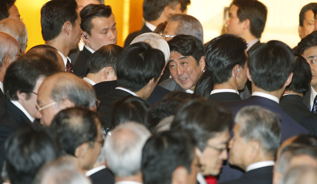 Japanese Prime Minister Shinzo Abe, center, talks with business leaders during Japan's business organizations joint New Year's party in Tokyo,  Monday, Jan. 7, 2013. Asian stocks cooled off Monday as