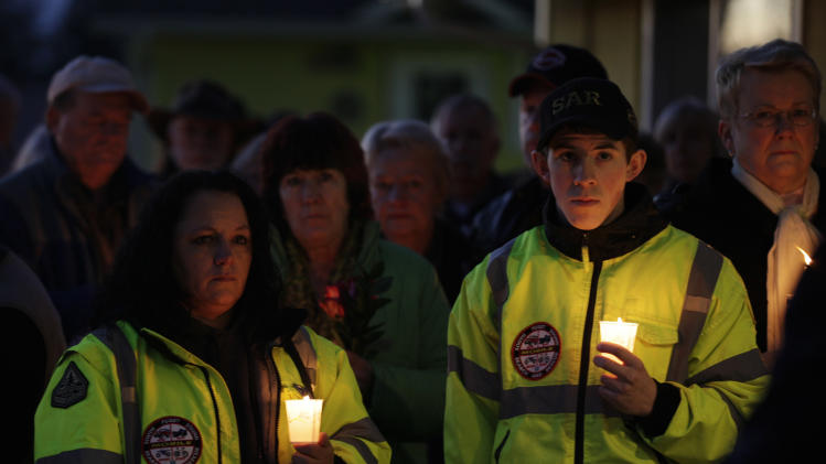 Members of the South Puget Sound Search and Rescue team stand with other mourners as they hold candles at an evening vigil for park ranger Margaret Anderson, Sunday, Jan. 8, 2012, in Eatonville, Wash. Anderson was killed by a gunman on Jan. 1, 2012, during a traffic stop where she worked at Moahaunt Rainier National Park. (AP Photo/Ted S. Warren)