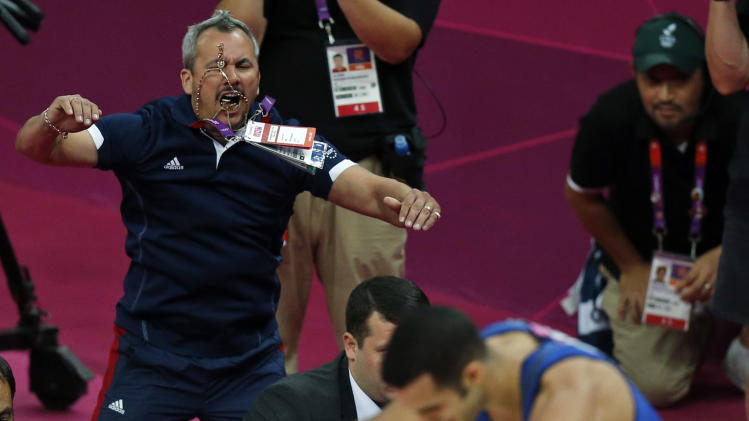 Stepfather and coach Yin Alvarez, left, celebrates after U.S. gymnast Danell Leyva's performance on the pommel horse during the Artistic Gymnastic men's individual all-around competition final at the 2012 Summer Olympics, Wednesday, Aug. 1, 2012, in London. (AP Photo/Matt Dunham)