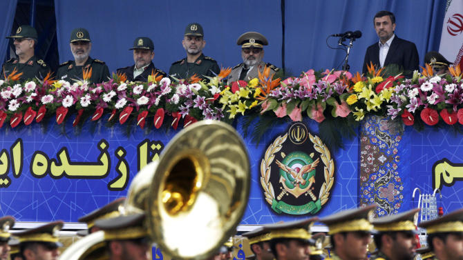 "Iranian President Mahmoud Ahmadinejad, right, reviews a military parade marking National Army Day, as he is accompanied by military commanders, in front of the mausoleum of the late revolutionary founder Ayatollah Khomeini, just outside Tehran, Iran, Thursday, April 18, 2013. Ahmadinejad slammed ""foreign presence"" in the Persian Gulf, claiming it's the source of insecurity in the region. (AP Photo/Vahid Salemi)"