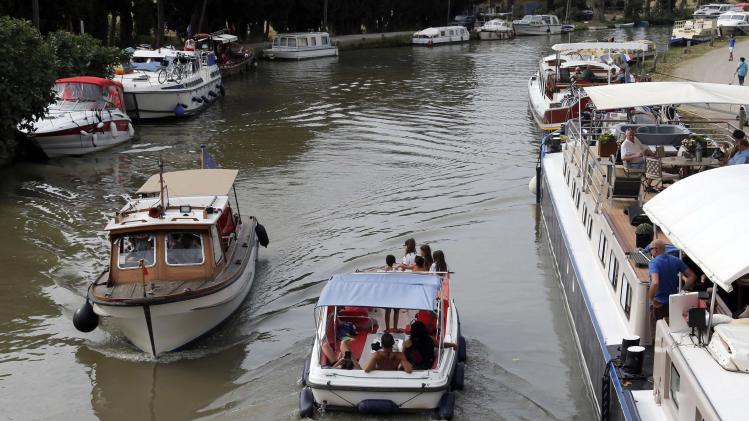 River boats with tourists make their way near others moored in the harbour of Le Somail along the Canal du Midi, southwestern France