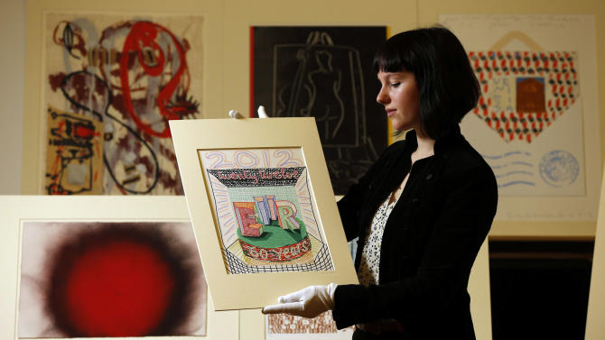An employee of the Royal Academy of Arts displays '2012 Queen Elizabeth II Diamond Jubilee' by David Hockney, as part of the Diamond Jubilee gift to Queen Elizabeth II, of almost one hundred works of art from the Royal Academy of Arts at the Queen's Gallery, Buckingham Palace, London, Friday Dec. 14, 2012. (AP Photo/PA, Jonathan Brady)  UNITED KINGDOM OUT  NO SALES  NO ARCHIVE